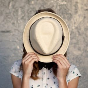 shy-woman-hiding-behind-hat-1527694118